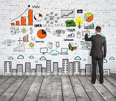 man drawing business strategy analytics on brick wall
